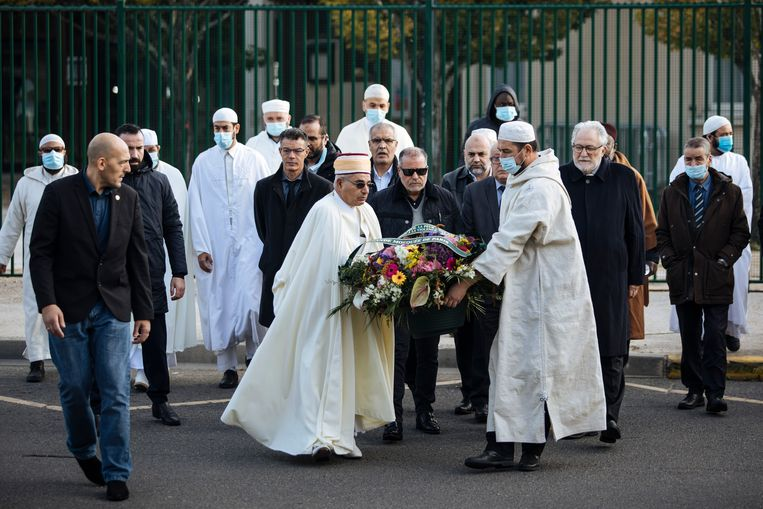 Imams van de Grote Moskee van Parijs legden gisteren bloemen voor de school  waar Samuel Paty lesgaf. In het hele land eerden scholen de docent geschiedenis  en maatschappelijke vorming die vorig jaar op 16 oktober door een geradicaliseerde  jihadist op straat werd onthoofd.  Beeld AP