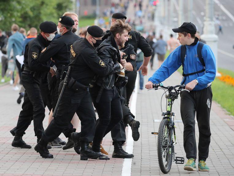 Politieagenten dragen beschermende maskers terwijl ze een demonstrant arresteren tijdens een protest in Minsk. Beeld EPA