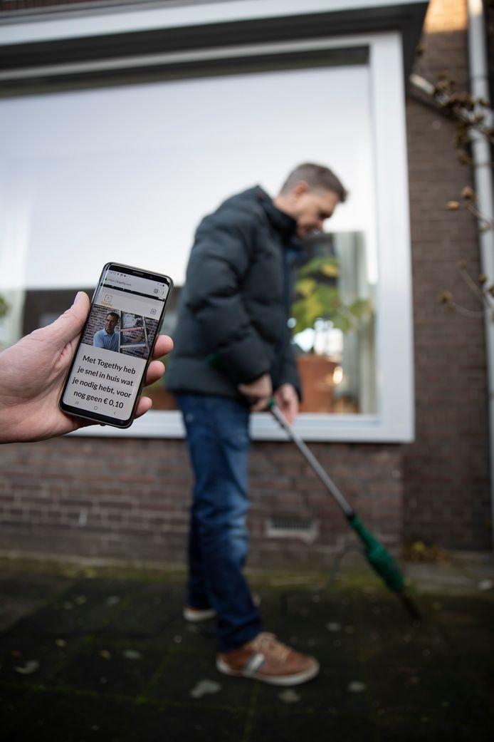 Initiatiefnemer Niek Huijsmans laat zijn app Togethy zien. Via de app kun je allerlei gebruiksapparaten delen. Bijvoorbeeld een onkruidverbrander.
