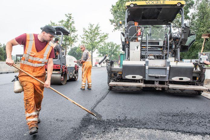 De asfalteerders leggen de laatste hand aan de weg.