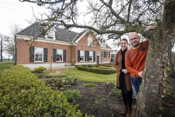 Ester en Ruud Geerligs  voor hun monumentale boerderij. Zij bewonen het linkerdeel, Ruuds ouders het rechter stuk.  In het midden de oude woonkamer.