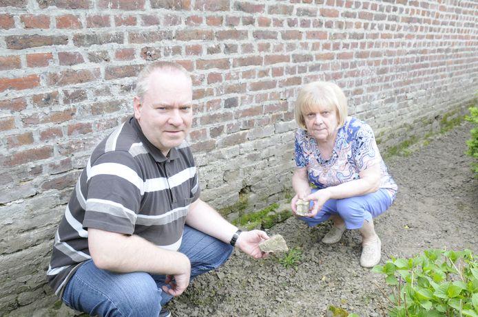 Michel Vandersteen en Frieda Janzegers tonen de schade aan de kerkhofmuur, die achteraan in de tuin van Frieda en Aimé uitkomt.