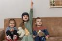 Isa op de bank met haar zusje en broertje.