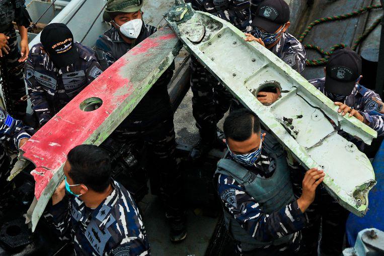Indonesische soldaten bergen brokstukken van het gecrashte vliegtuig. Beeld AP