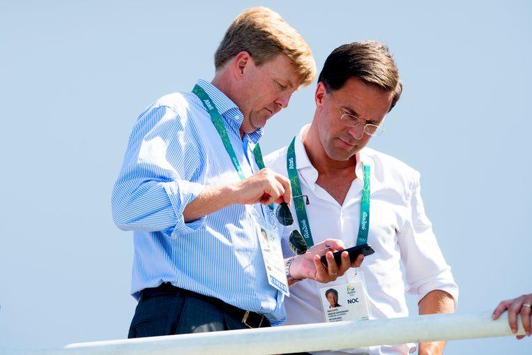 Willem-Alexander en Mark Rutte op de tribune naar het roeien in het Lagoa Rodrigo de Freitas tijdens de Olympische Spelen van Rio.  Beeld ANP