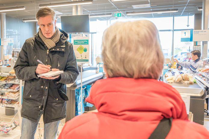 Verslaggever Rolf Bosboom in gesprek met mevrouw Van der Veen tijdens het winkeluurtje voor zeventigplussers in Goes.