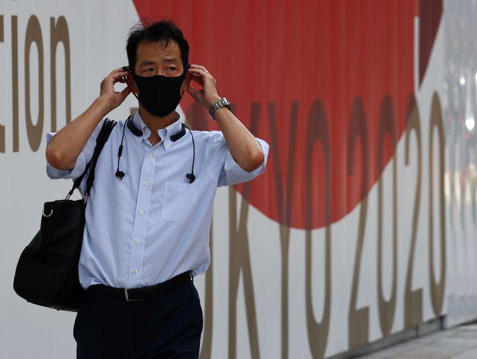 Un homme portant un masque passe devant un panneau des Jeux olympiques de Tokyo 2020 à Tokyo, au Japon, le 28 juillet 2021.