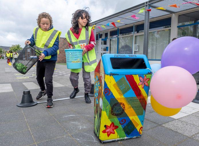 Jermaylon (links) en Kotouf van basisschool de Leeuwenburch deden vrijdag mee met een afvalrace waarmee de nieuwe, door leerlingen zelf beschilderde afvalbak op het schoolplein in gebruik is genomen.