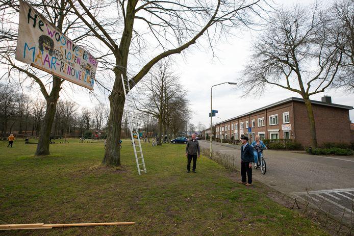 Wim de Gouw (L) en Theris Boom hangen een spandoek op aan de Pastoor Smoldersstraat in Vlijmen, de huizen staan op de nominatie om gesloopt te worden. Het blok erachter (oranje daken) wordt gerenoveerd.