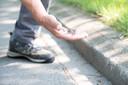 Willem raapt veel stalen pinnen op langs de stoepranden die van de staalborstels afvallen van Prop Onderhoudservice.