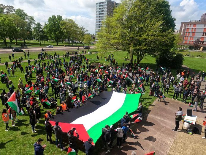 De demonstraten houden gezamenlijk de vlag vast.