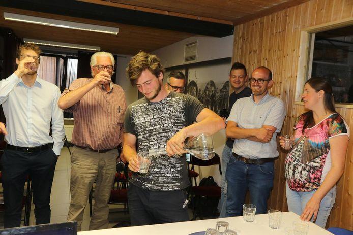 Medewerkers van het project schenken zichzelf een glaasje water, gedestilleerd uit urine, uit.