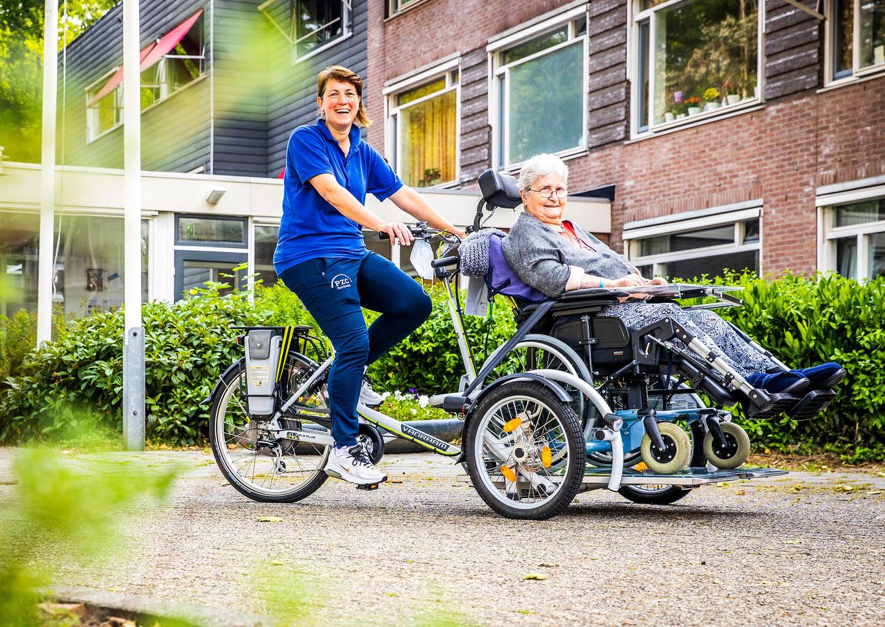 Bewegingsagoog Margriet de Mol en bewoonster Elly de Kruyf op de gloednieuwe rolstoelfiets.