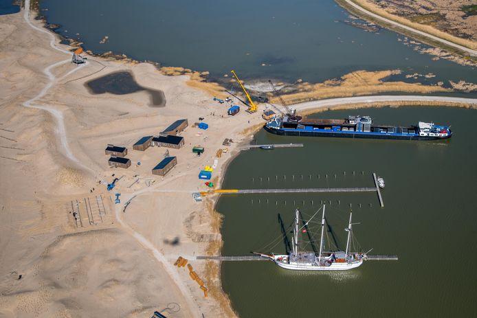 Een schip levert gebouwtjes af voor de nederzetting op de Marker Wadden.