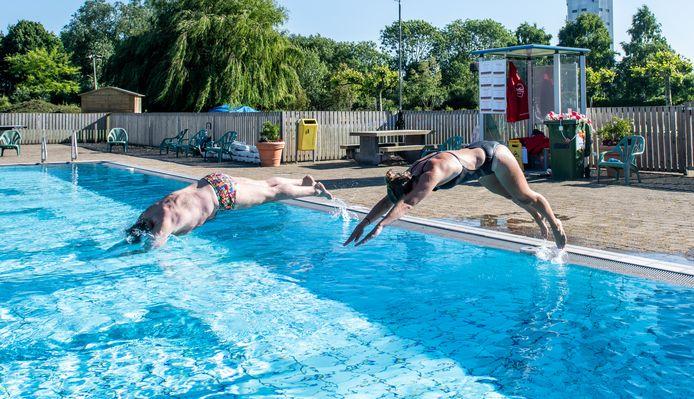 Ardi Boenink en Suzanne Driessen maken een duik in het buitenbad van zwembad De Hoorn in Alphen aan den Rijnd