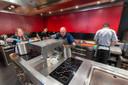 Chef-kok Dennis Middeldorp (midden) temidden van het personeel en leerlingen in de keuken van restaurant Sense.