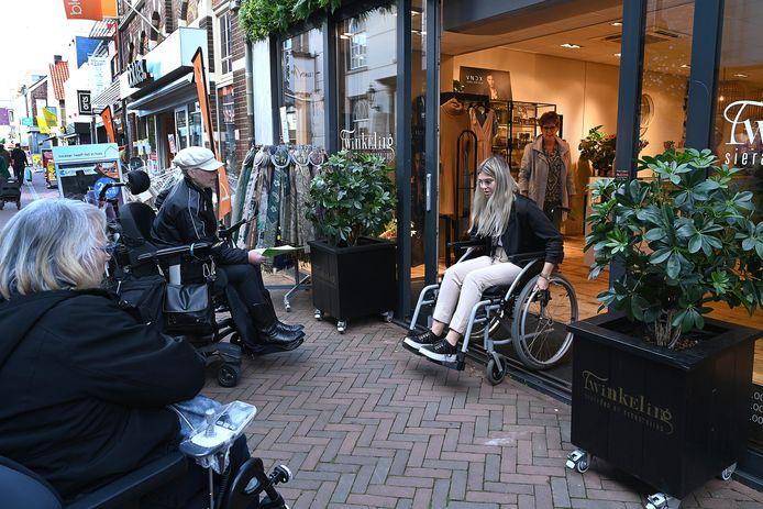 Emily van Vorsellen van kledingwinkel Twinkeling in Boxmeer ervaart zelf hoe het is om met een rolstoel een drempel te overwinnen. José Lichteveld (links) en Jeannette Schröter kijken of het lukt.