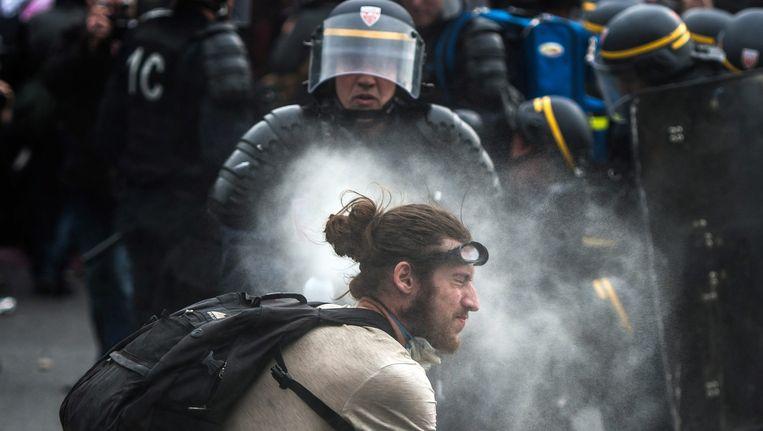 Een Franse agent spuit met traangas in de richting van een demonstrant bij een demonstratie in Parijs. Beeld EPA
