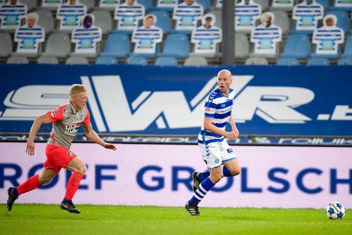 Elmo Lieftink aan de bal tegen FC Eindhoven, op de achtergrond de kartonnen De Graafschap-supporters van de actie 'Smoel op de Stoel'.