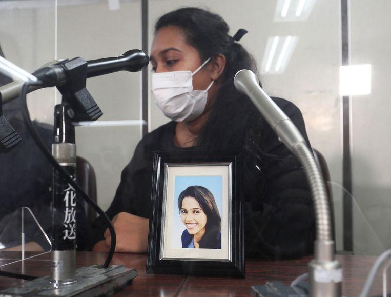 Poornima Wishma met een foto van haar zus, Ratnayake Liyanage Wishma Sandamali, tijdens een persconferentie in Tokyo. Beeld AFP