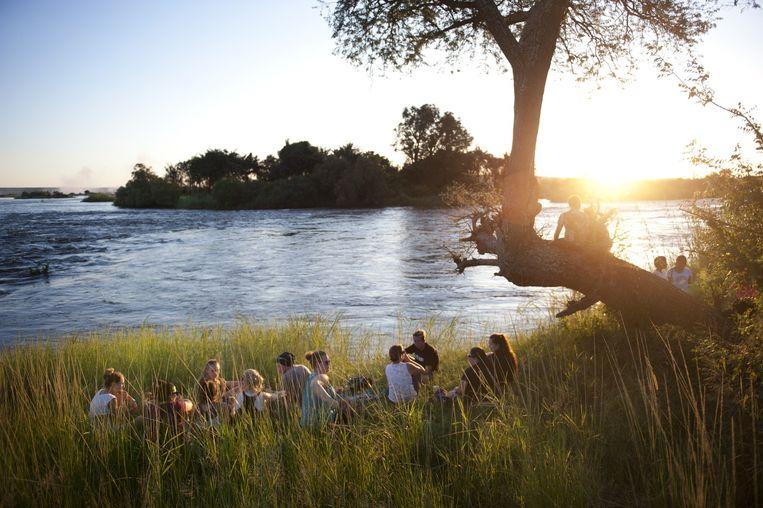 Na het vrijwilligerswerk is het goed gin-tonics drinken bij zonsondergang, aan de oever van de Zambezi-rivier. Beeld An-Sofie Kesteleyn