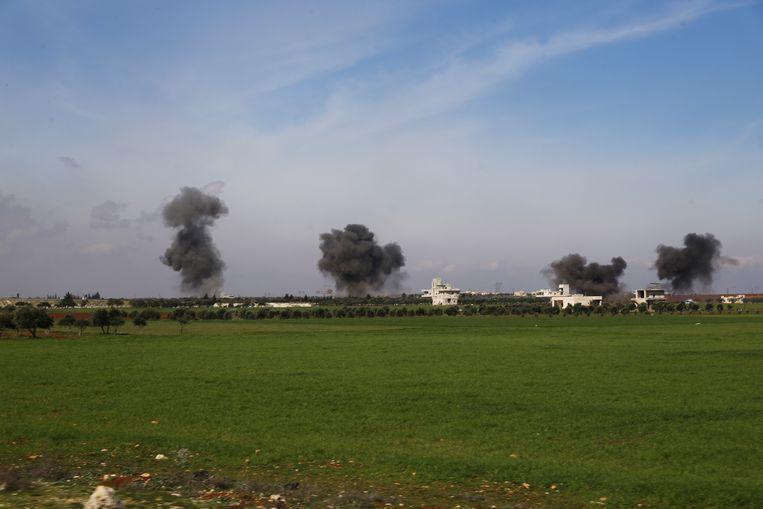 Rookpluimen stijgen op na een luchtaanval bij de stad Saraqeb, in de Syrische provincie Idlib.  Beeld AP