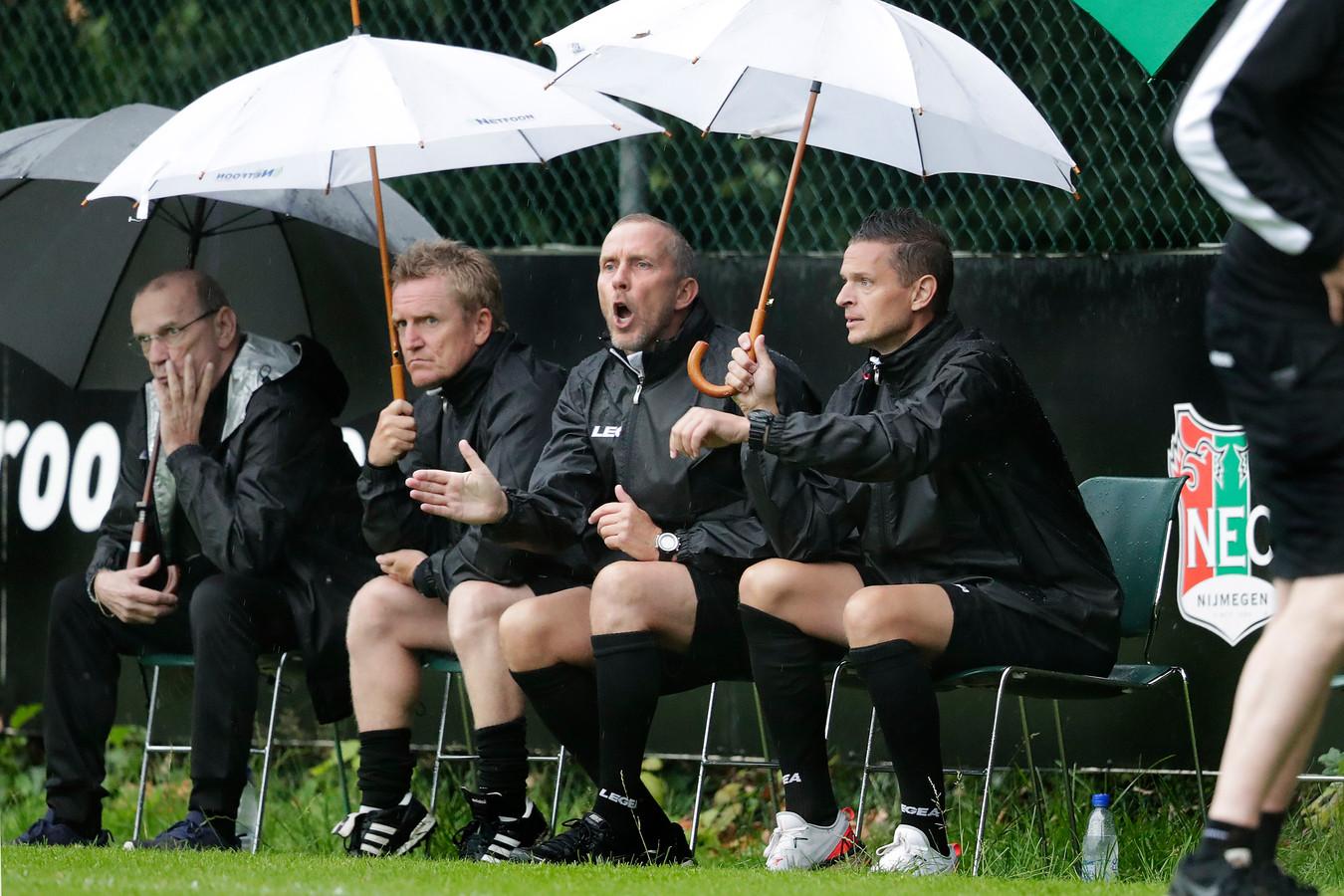 François Gesthuizen, Adrie Bogers en Rogier Meijer (vlnr) schuilen onder twee witte paraplu's voor de regen.