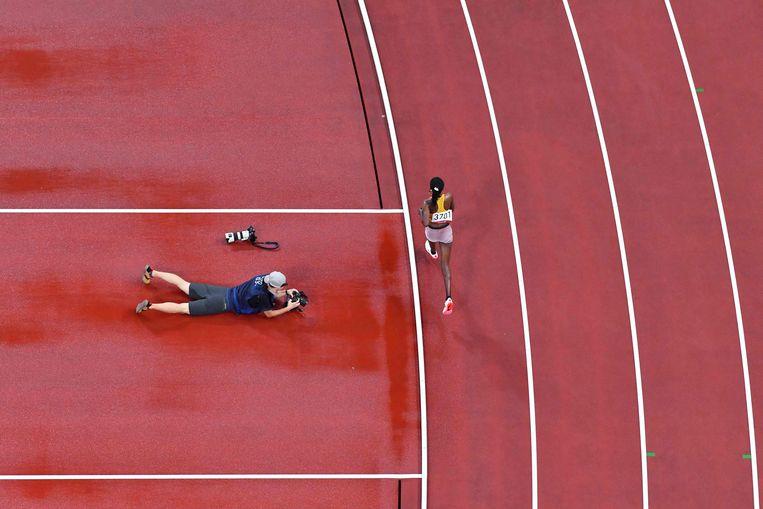 Een fotograaf controleert zijn werk naast de atletiekbaan in het Olympisch Stadion in Tokio. De Oegandese Prisca Chesang rent ondertussen voorbij tijdens de 5000 meter.  Beeld AFP