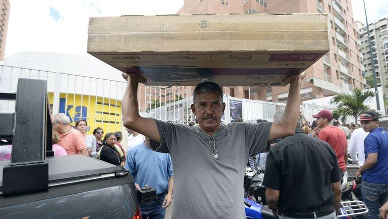 Een man tilt een lcd-tv boven zijn hoofd nadat hij heeft geshopt bij een vestiging van de elektronicaketen Daka in de Venezolaanse hoofdstad Caracas. Beeld afp