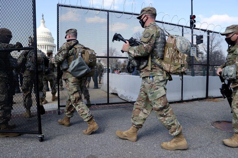 Soldaten van de Nationale Garde betreden het terrein van het Capitool. Beeld REUTERS