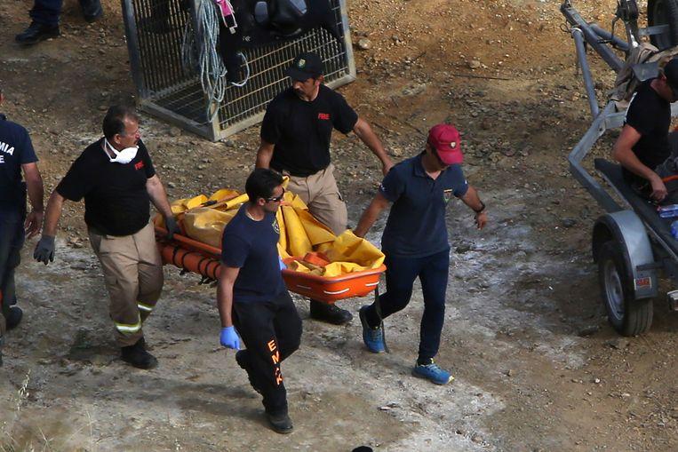 De politie van Cyprus draagt de tweede gevonden koffer weg voor onderzoek. Beeld AP