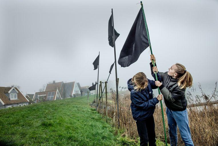 Uit protest tegen dijkverzwaring planten kinderen zwarte vlaggen bij Uitdam.  Beeld Jean-Pierre Jans / HH