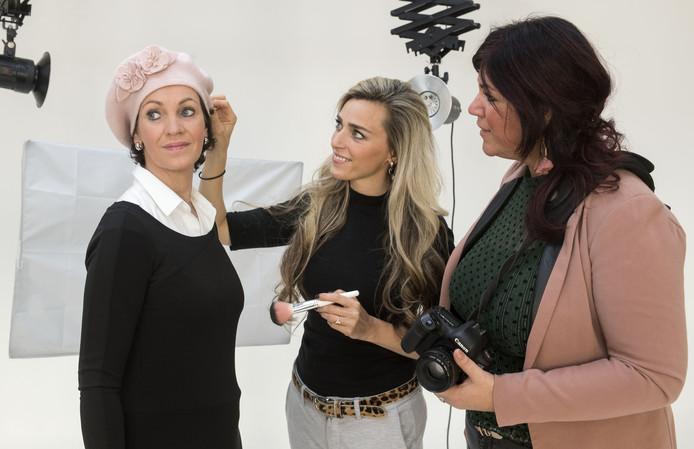 Fotografe Suzan Reuvers (rechts) en visagiste Fardau Blom (midden) zorgen ervoor dat Simone Meenhuis er stralend uitziet tijdens de Pink Ribbon Night.