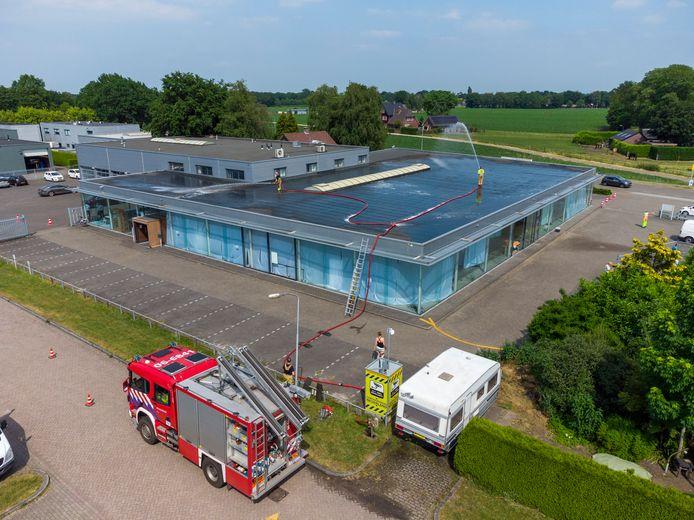 Vanwege extreme hitte wordt het dak van de priklocatie in Heerde door de brandweer gekoeld. Beneden hangen al rondom witte doeken tegen de zon