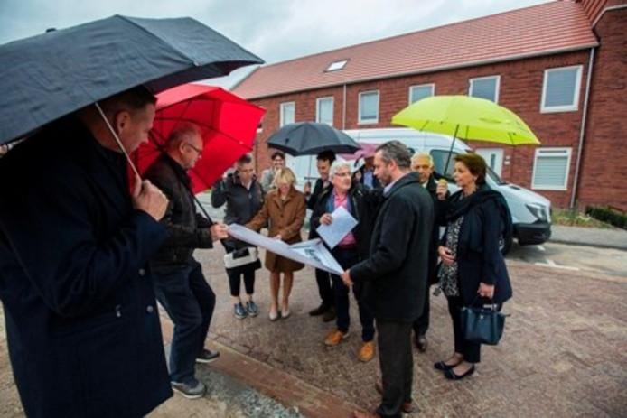 Opbouwwerker Leo Litjens van de LEVgroep geeft uitleg over het Markiesveld aan het college van B&W. Voorzitter van de wijk raad Willem Zerstegen (rode paraplu) houdt de werktekening vast.