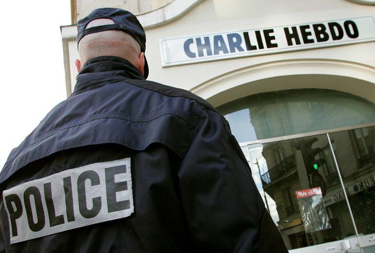 Een agent houdt wacht bij de redactie van Charlie Hebdo. Beeld reuters