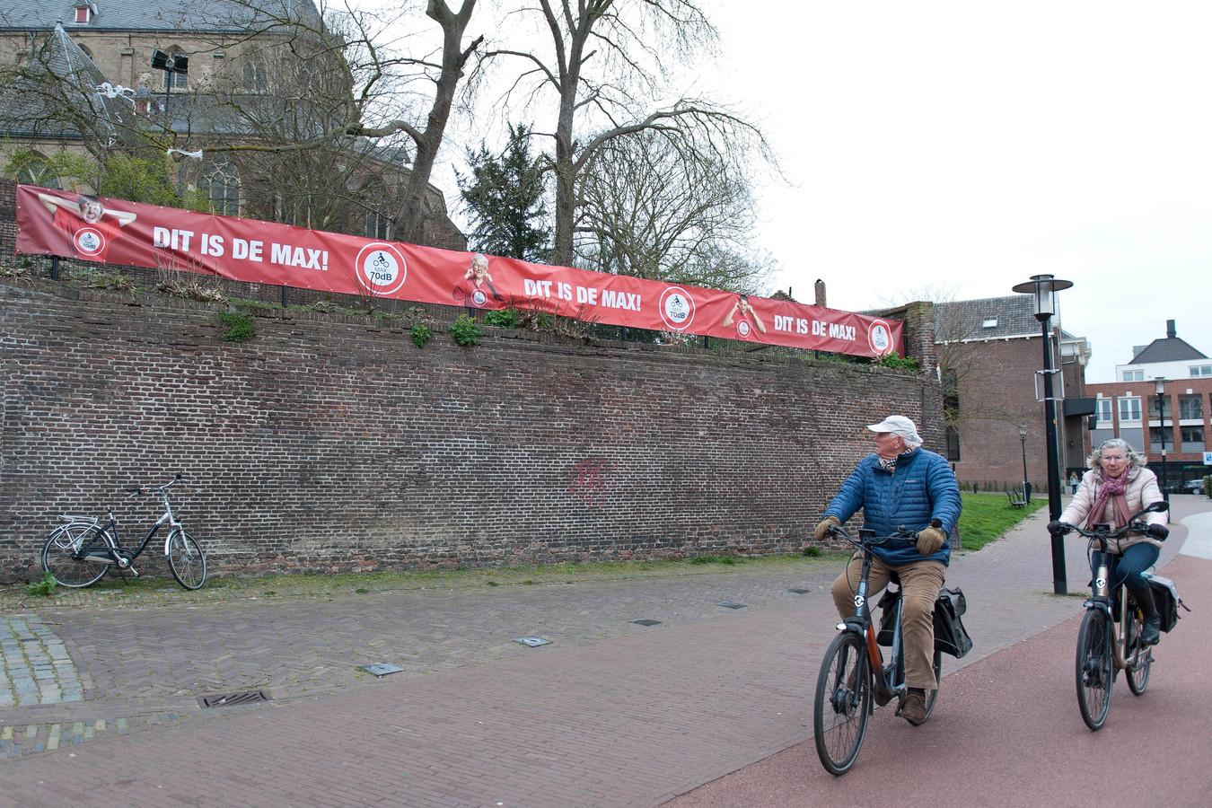 Een fietser werpt een blik op de spandoeken tegen het motorlawaai in Deventer. Op de achtergrond de Bergkerk.
