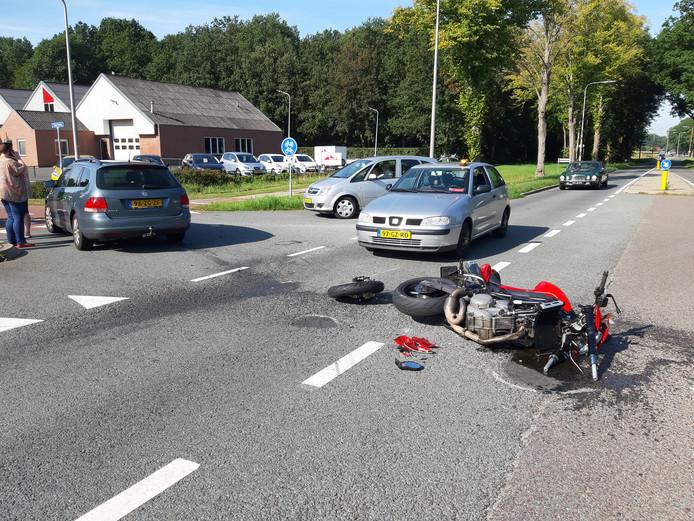 Een motor ligt in stukken op de weg na een flinke botsing met een personenauto.