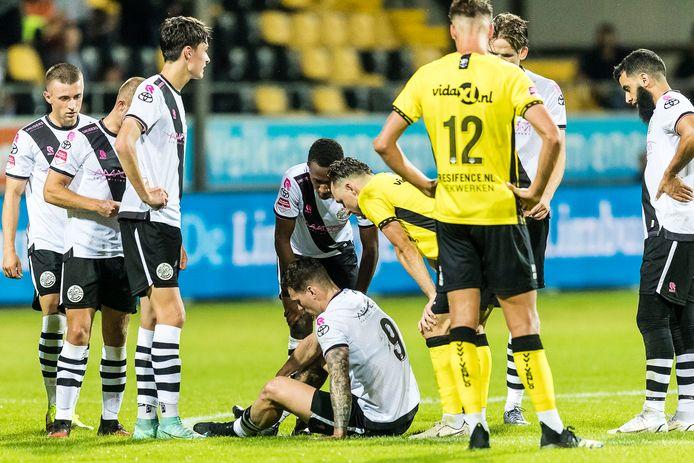 Jizz Hornkamp zit aangeslagen op het veld na zijn botsing met VVV-doelman  Lukas Zima. De spits van FC Den Bosch moest het veld daarna verlaten met rugklachten.
