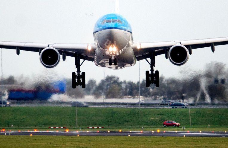 Een vliegtuig landt door een storm bijna haaks op de baan op Schiphol. Beeld ANP