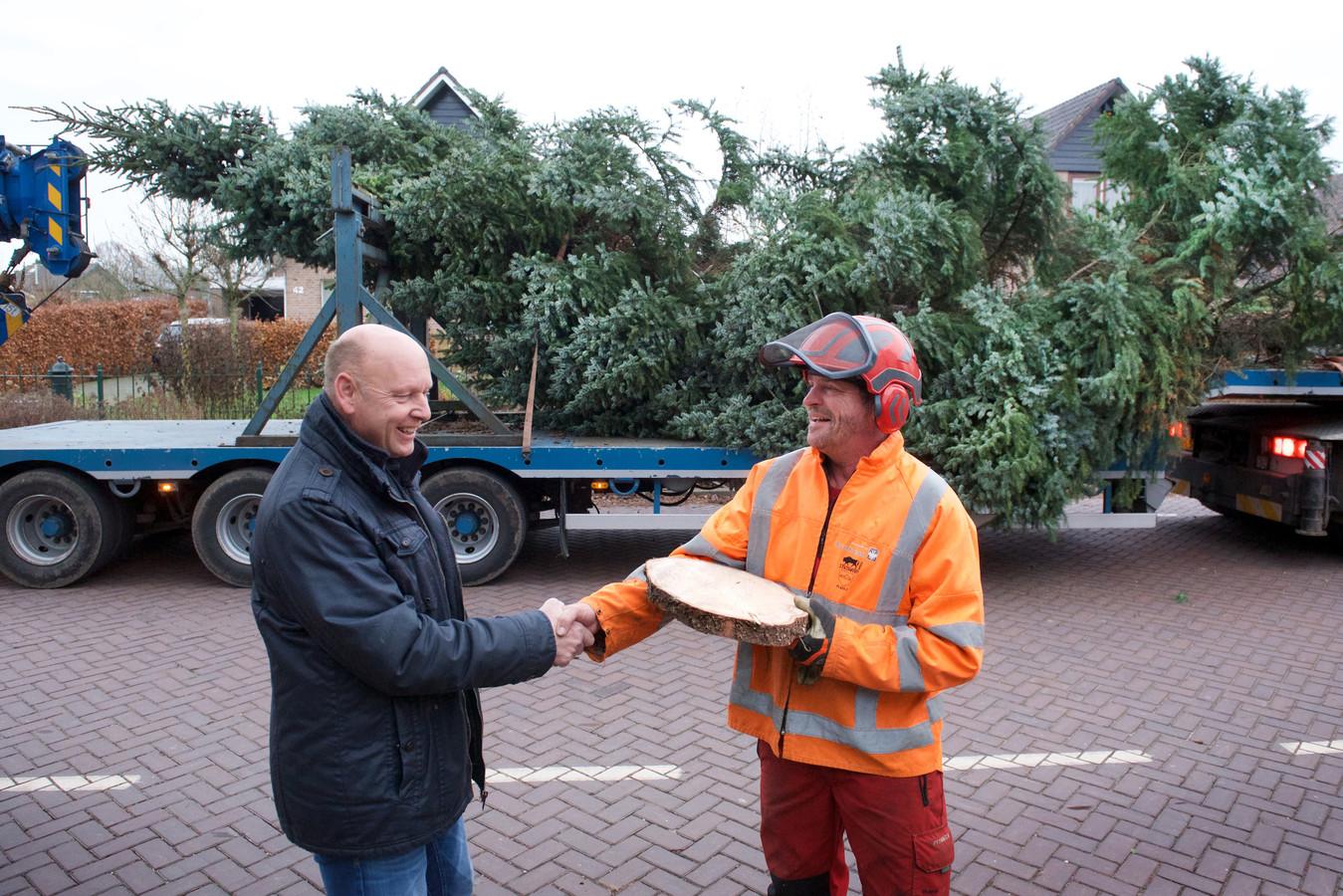 Eldenaar Derk-Jan Hulstein (links) krijgt een schijf van de blauwspar uit zijn voortuin als aandenken. De boom krijgt een kort tweede leven als kerstboom in Schuytgraaf.