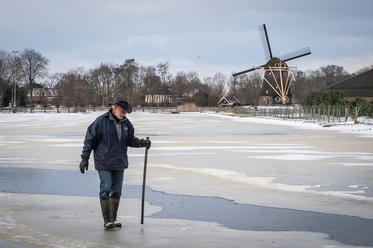 Wim test het ijs, dat een centimeter gegroeid is en op sommige plaatsen zelfs twee centimeter. Beeld Dingena Mol