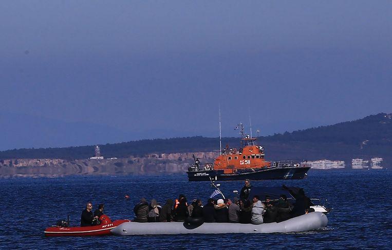 Een boot vol vluchtelingen nadert het Griekse eiland Lesbos, onder het oog van de Griekse kustwacht. Beeld Photo News