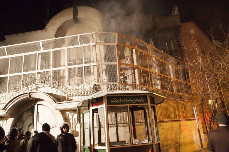 Woedende betogers staken een deel van de Saoedische ambassade in Teheran in brand. Beeld PHOTO_NEWS