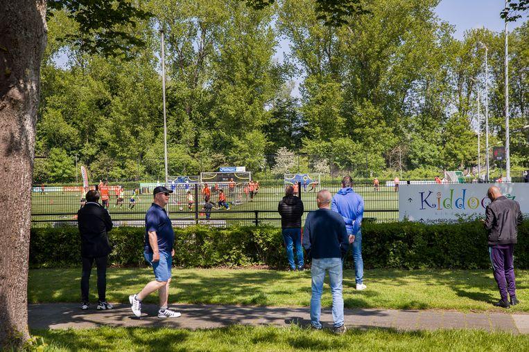Voetbalvereniging R.K.S.V. Spartaan'20 in Rotterdam, zondagmiddag. Terwijl de jeugd traint, kijken de ouders van buiten het terrein toe.  Beeld Arie Kievit