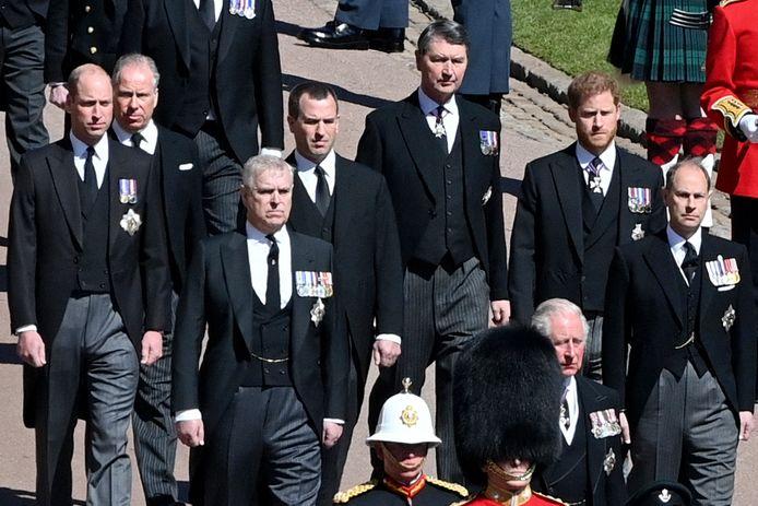 Prins William (links) en prins Harry (tweede van rechts) lopen gescheiden van elkaar achter het voertuig met de kist aan