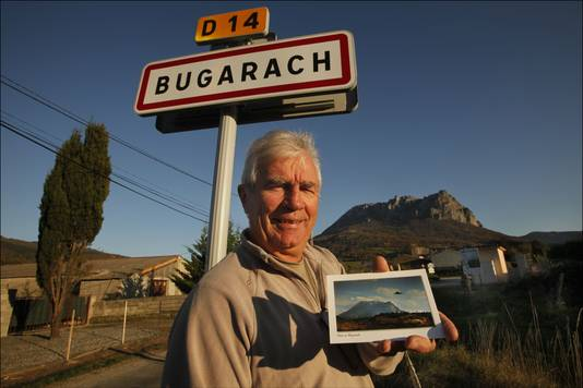 Burgemeester Jean-Pierre Delord met een postkaart van Bugarach waarop een UFO is gemonteerd.