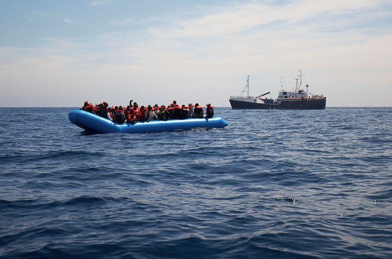 Migranten in een rubberen boot met op de achter grond het reddingsschip van Sea Watch.   Beeld AP