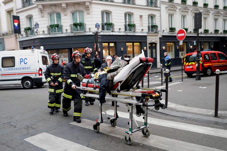 Brandweermannen voeren een gewonde af. Beeld AFP