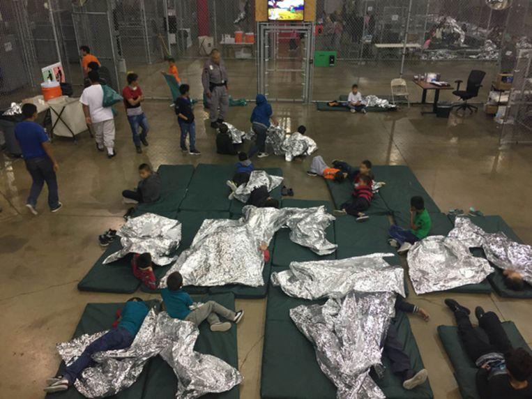 Kinderen liggen onder foliedekentjes in een verwerkingscentrum van de Customs & Border Protection (CPB) in McAllen, Texas. Beeld EPA